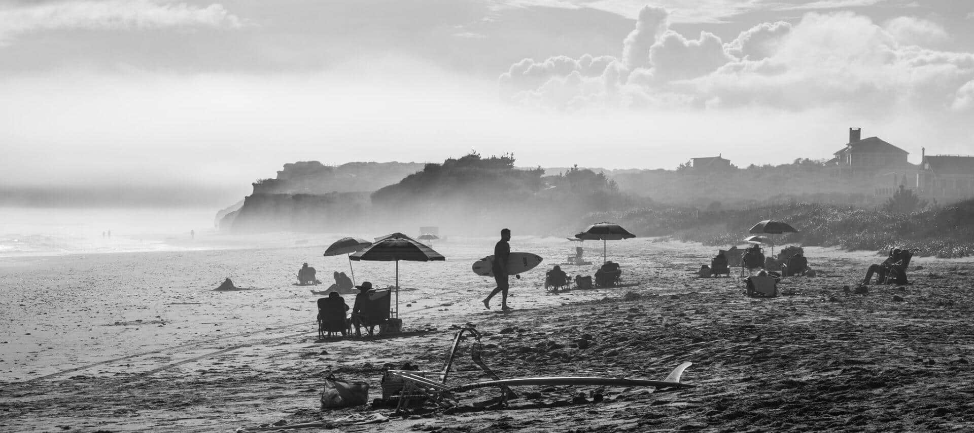 Black and white of people on beach sunbathing and surfing, with misty view of mountains in the background
