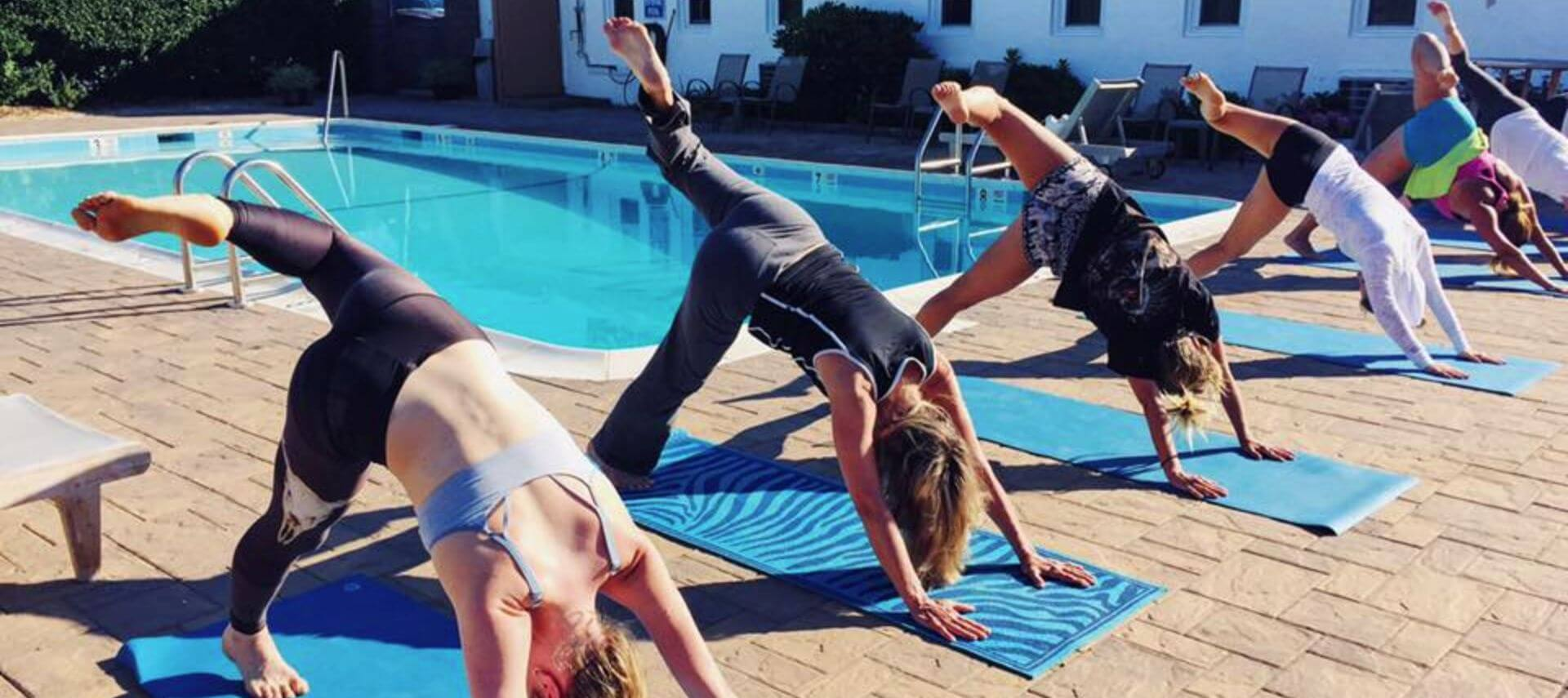 Four women doing three-legged dog yoga pose on blue mats at poolside