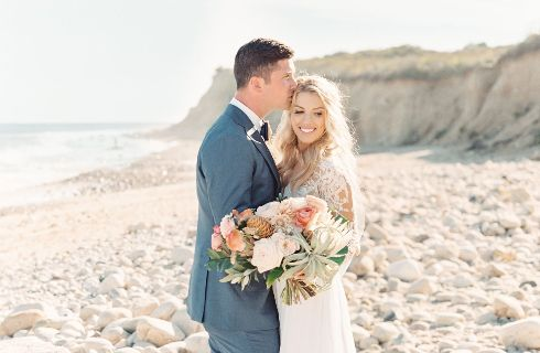Young bride and groom embrace on the beach - he in a grey tuxedo, she in a white gown.